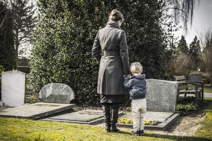 26592865 - A photo of a woman and child looking at gravestone on graveyard