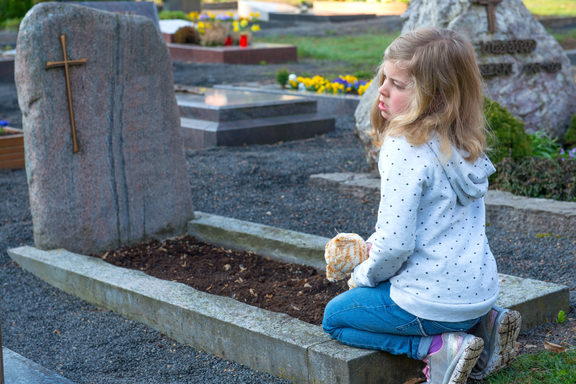 A photo of a little sad girl in front of grave