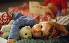 A preschooler clutches a teddy at sleep time at daycare.