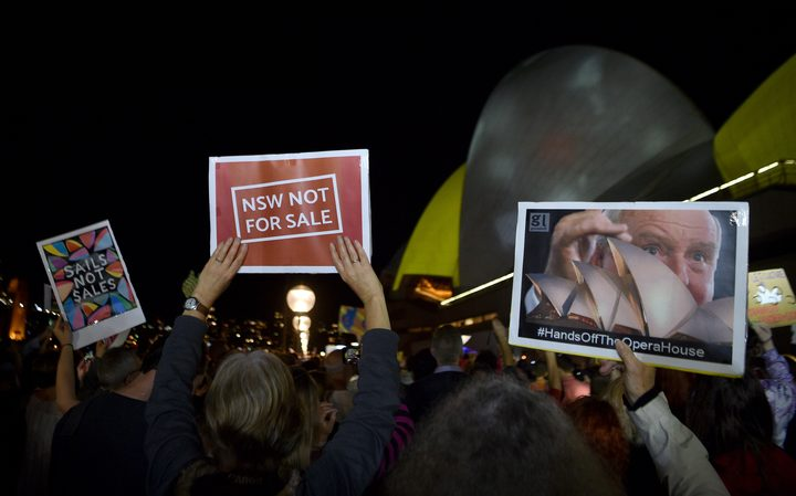 Protesters hold up signs outside the Sydney Opera House as it is lit up with advertising for the upcoming Everest Cup horse race