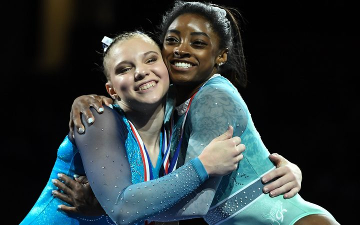 Gymnasts Simone Biles and Jade Carey share a hug on the awards podium at a recent competition in Boston.