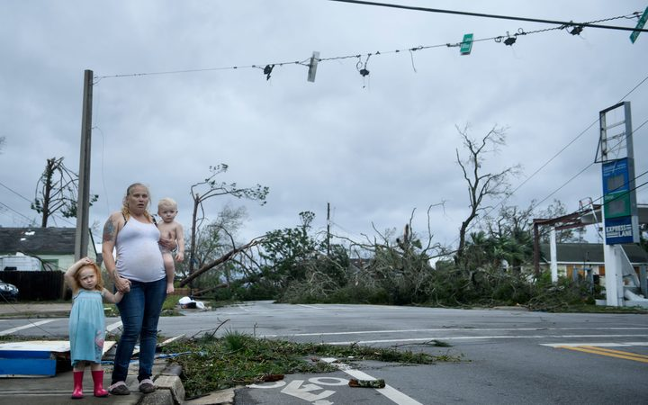 A woman and her children stand near a destroyed gas station after Hurricane Michael in Panama City.