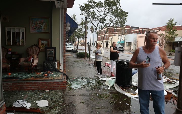 People walk past damaged stores after hurricane Michael passed through the downtown area of Panama City in Florida.
