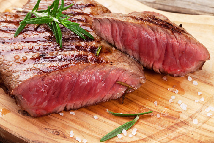 50344317 - grilled beef steak with rosemary, salt and pepper on cutting board