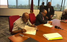 Bougainville president John Momis, left, and former PNG Prime Minister Peter O'Neill sign the agreement on the question for the independence referendum.