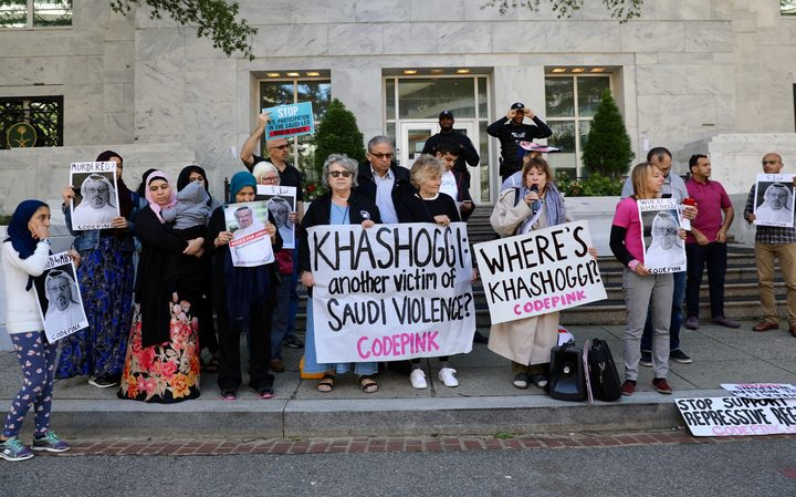 A group of people  hold pictures of missing Saudi journalist Jamal Khashoggi during a demonstration in front of the Embassy of Saudi Arabia in Washington.