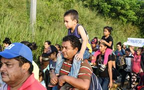An Honduran man carries a child on is shoulders during an exodus towards the US from San Pedro Sula