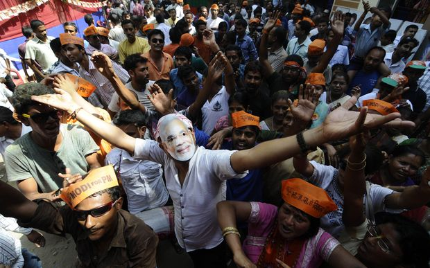BJP workers, one wearing a mask of Narendra Modi, celebrate outside the party office in Guwahati.