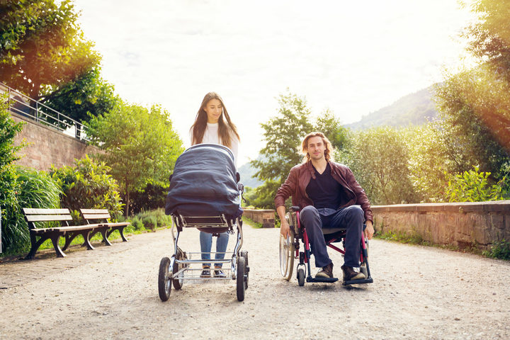 A photo of young parents enjoying time outdoors, taking their baby to a park. The father is sitting in a wheelchair.