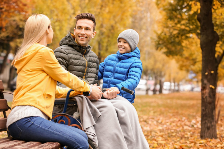 A photo of a Man in wheelchair with his family outdoors on autumn day