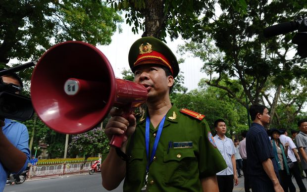 A policeman uses a megaphone to ask people not to gather on a street near the Chinese embassy in Hanoi.