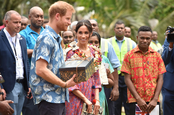 Prince Harry and wife Meghan, Duchess of Sussex, receive a gift from the University of the South Pacific in Suva.