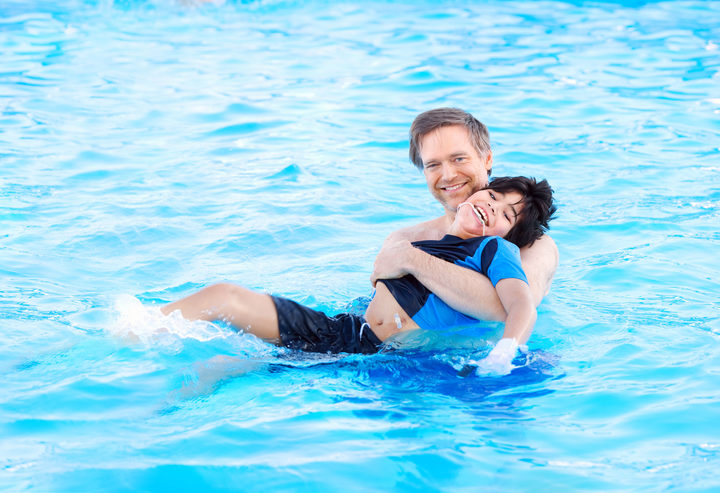 A photo of a father swimming in a pool with his biracial disabled son in his arms. The child has cerebral palsy.