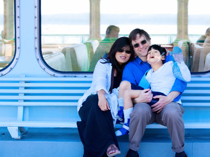 A photo of a smiling multiracial, interracial couple holding disabled son on ferry boat deck. Their child has cerebral palsy.