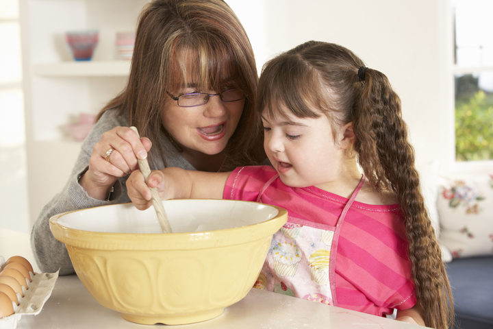 A photo of a girl with downs syndrome baking with mother