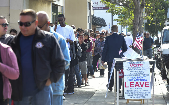 People wait in a long line to purchase lottery tickets outside the Blue Bird Liquor store in Hawthorne, California.