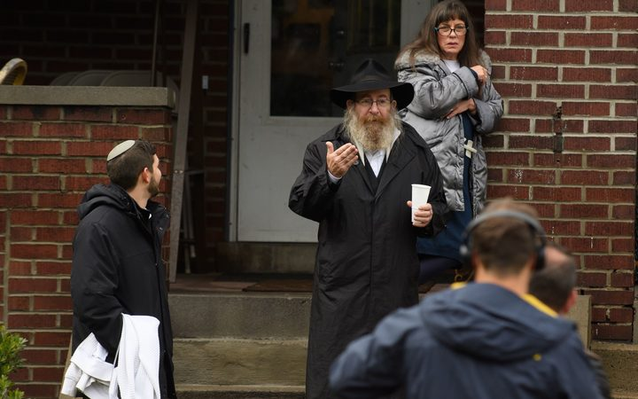 Residents talk to the media near the site of a mass shooting at the Tree of Life Synagogue in the Squirrel Hill neighborhood on October 27, 2018 in Pittsburgh, Pennsylvania.