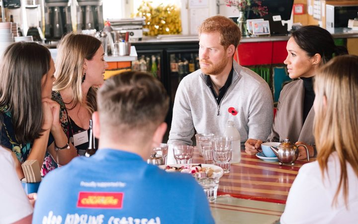 Prince Harry and Meghan, Duchess of Sussex, talk to Jazz Thornton and Gen Mora, the founders of Voices of Hope at the Maranui Cafe in Wellington
