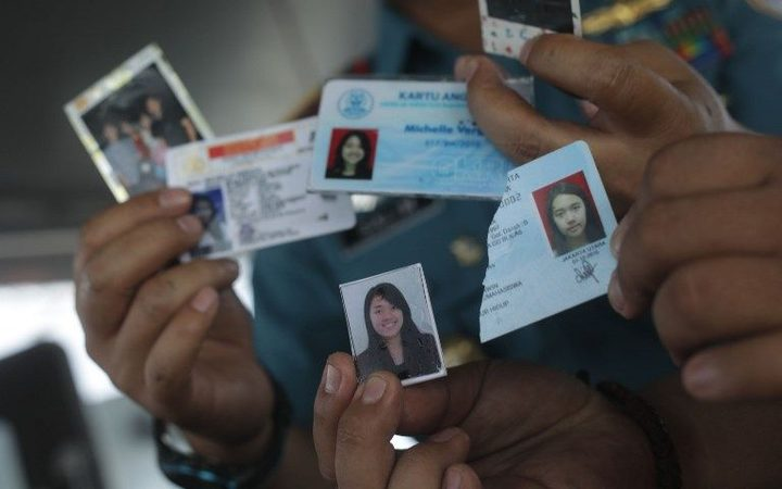 Searchers show IDs and photos found in the water after the Lion Air JT 610 plane crashed.