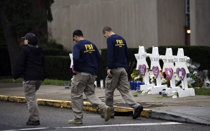 FBI officers walk past a memorial outside the Tree of Life synagogue in Pittsburgh after a shooting there left 11 people dead.