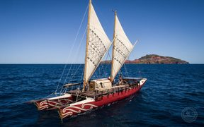 The Haunui, a double-hulled voyaging waka, out on the open waters.