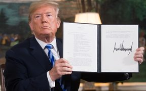 In this file photo taken in May 2018 US President Donald Trump signs a document reinstating sanctions against Iran