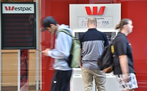 A man uses an ATM machine outside a branch of the Westpac bank in Sydney. Generic.