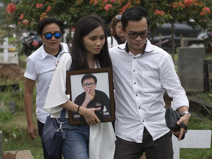 The sister of Hizkia Jorry Saroinsong, a passenger on the Lion Air flight, carries her brother's portrait during his funeral in Jakarta.