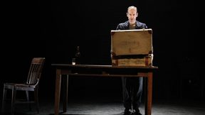 Denis O'Hare stands on a dark stage in front of a suitcase on a table.
