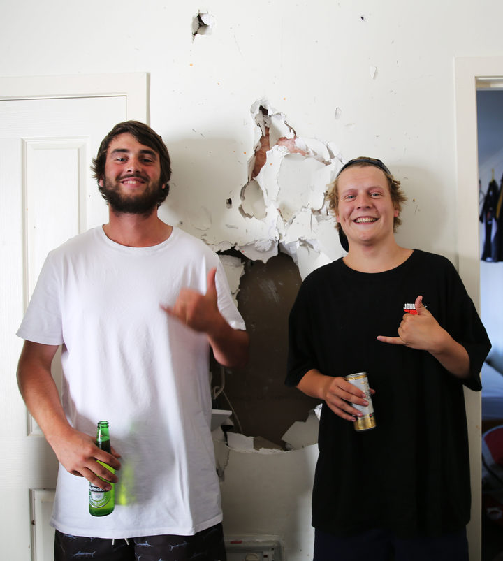 Max Lynch and Speedy pose next to a hole in their living room wall.
