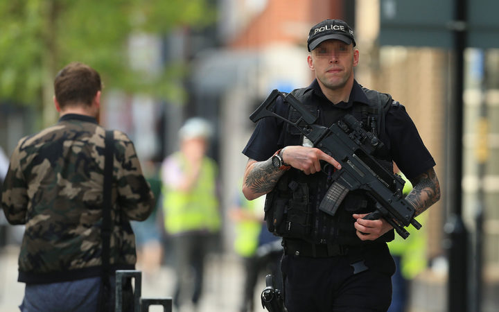 An armed police officer patrols the streets of Manchester.
