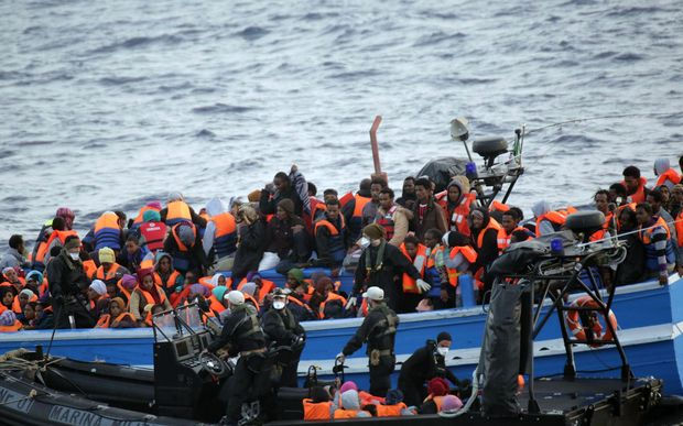Migrants sit in a boat during a rescue operation off the coast of Sicily in May.