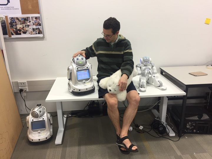 Dr Craig Sutherland with with an iRobi, a Paro and Nao.