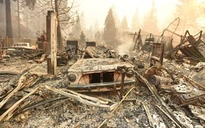 The burned remains of a vehicle and home are seen during the Camp fire in Paradise