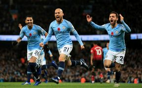 David Silva of Manchester City celebrates with teammates Riyad Mahrez and Bernardo Silva.
