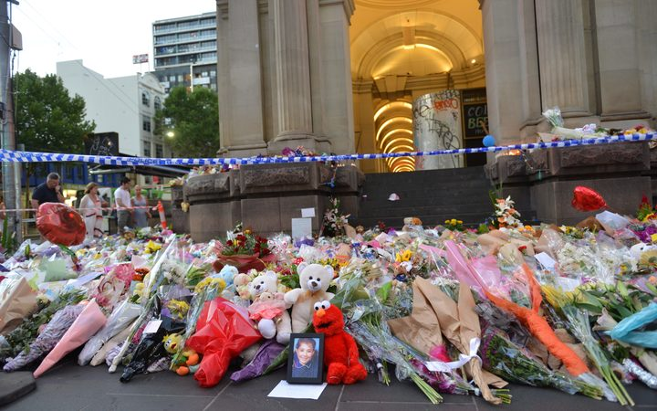 People lay flowers on Bourke street in Melbourne on January 22, 2017, after after a man went on a rampage in a car.