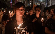 People hold candles to commemorate the Tiananmen Square anniversary.