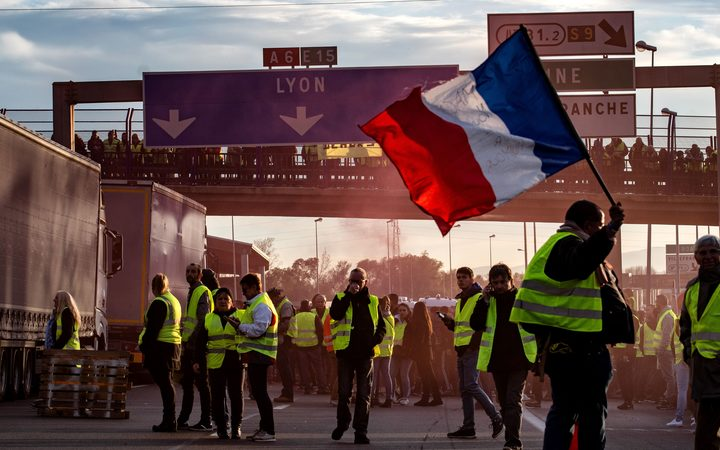 "A ""Yellow Vest"" (Gilets Jaunes in French) protester waves a French flag on the A6 motorway in Villefranche-sur-Saone on November 24, 2018."