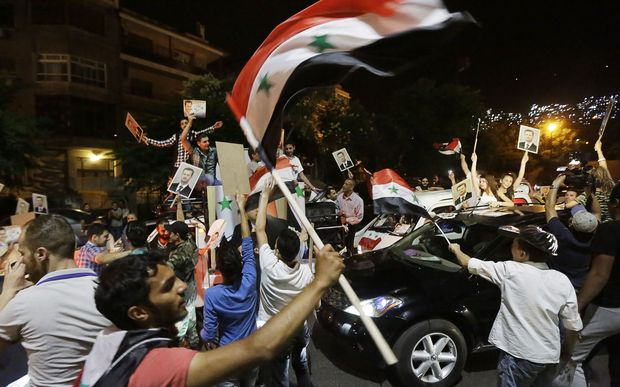 Syrians celebrate the vote's outcome in the capital Damascus.