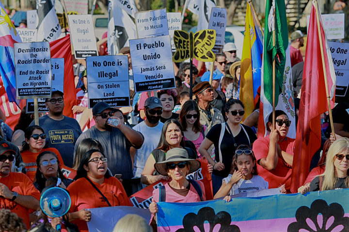 Protesters march along the United States-Mexico border during a rally to show solidarity with the migrant caravan on November 25, 2018.