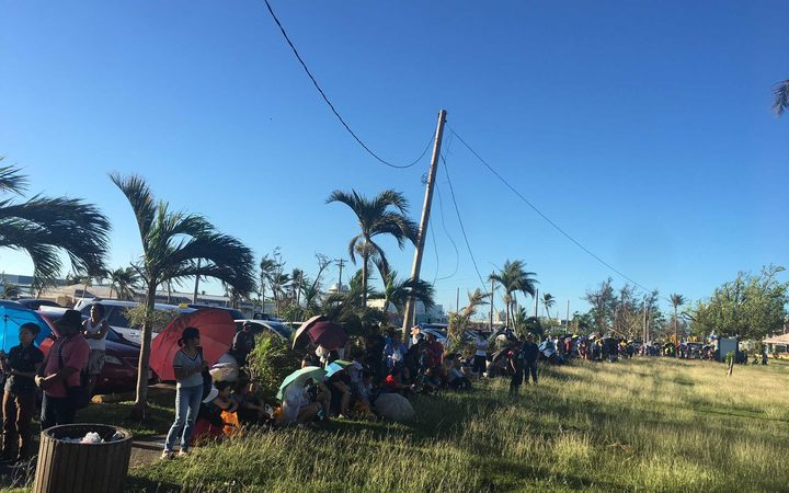 People lining up in the heat in the CNMI to get food stamps.