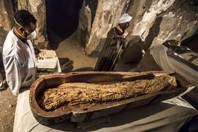 "November 24, 2018: Egyptian workers and archaeologists standing next to an opened intact sarcophagus containing a well-preserved mummy of a woman named ""Thuya"", discovered at Al-Assasif necropolis in Luxor, Egypt"
