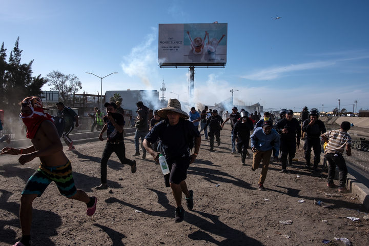Central American migrants - mostly Hondurans - run along the Tijuana River near the El Chaparral border crossing in Tijuan, after the US border patrol threw tear gas from the distance to disperse them.