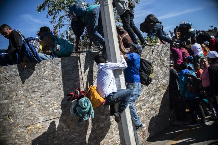 A group of Central American migrants- mostly from Honduras- get over a fence as they try to reach the US-Mexico border