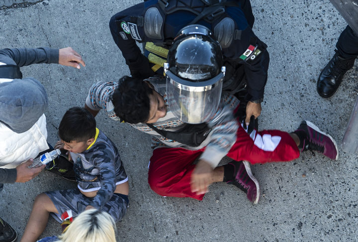 Central American migrants are stopped by Mexican police forces as they reach the El Chaparral border crossing in Tijuana Baja California State Mexico
