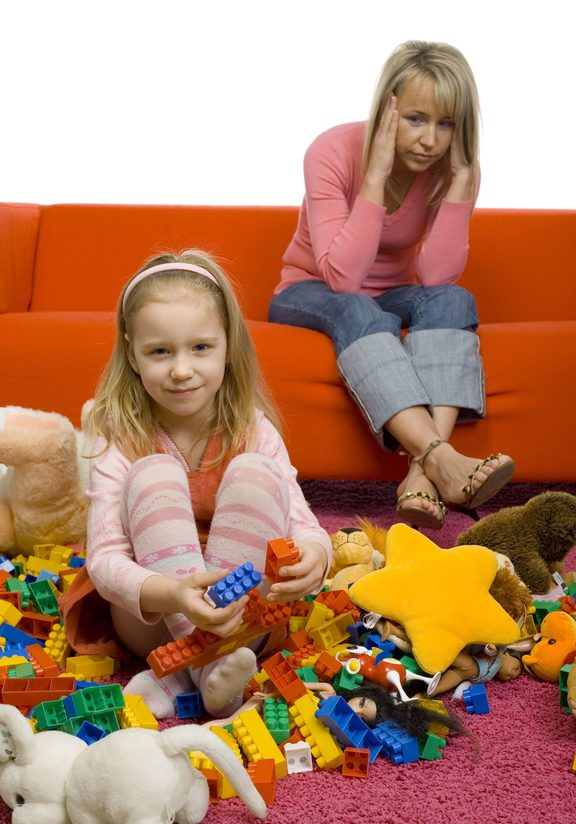 917736 - 5-6yo girl with her toys on the floor. there's huge mess. there's mother sitting on couch behind girl. mother has headache cause this mess.
