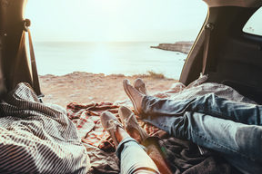 Man and woman relaxing inside trunk and watching at the sea. Fall car trip in sunset. Freedom travel concept. weekend.