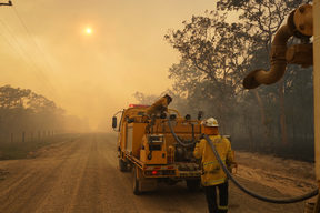 Firefighters refill their water from a water tanker in Pacific Drive in Deepwater National Park area of Queensland.