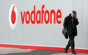 man with mobile phone walking past Vodafone sign