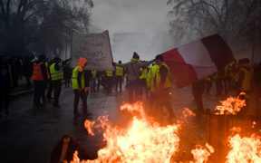 Demonstrators carry a French flag during a protest of Yellow vests (Gilets jaunes) against rising oil prices and living costs, on December 1, 2018 in Paris.